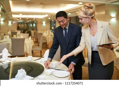 Wedding planner and banquet manager discussing table setting