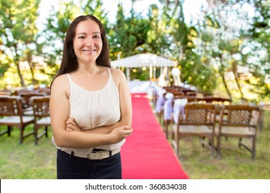 wedding planner woman  is organizing  the wedding reception venue for her customers standing and smiling at the wedding place