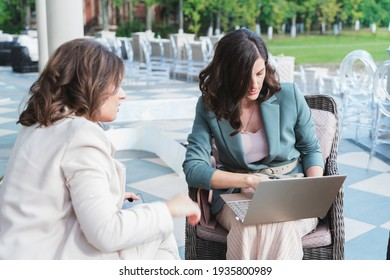 Wedding planners, organizers, event decorators, managers with laptop.Business meeting,negotiations,project discussion,signing contract with client,customer.Women, girls in stylish suits in restaurant.