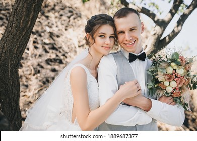 Wedding portrait of a stylish groom with a bouquet in his hands and a cute bride in a long white dress and curly hair on a nature background near tree branches.