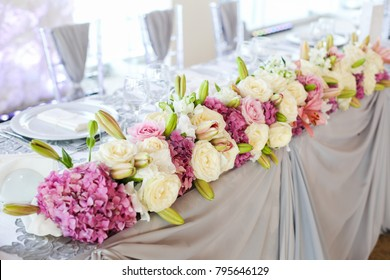 Wedding presidium in restaurant, free space. Wedding banquet table for newlyweds with flowers
