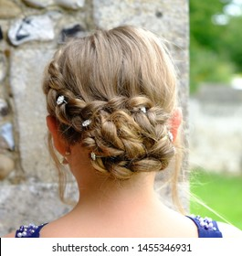 Wedding or prom hair in plaits/braids updo in a bun dark blonde with wispy strands, sparke pins to hold in place