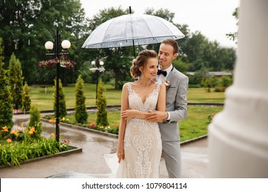 Wedding rain. Bride and groom in the rainy weather are covered with a transparent umbrella, rain drops
