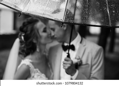 Wedding rain. Bride and groom in the rainy weather are covered with a transparent umbrella and kisses. Selective focus on rain drops in umbrella