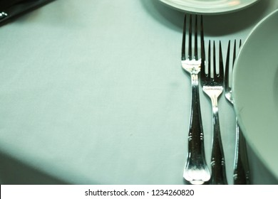 Wedding reception banquet dinner party table place settings set in luxury hotel venue.