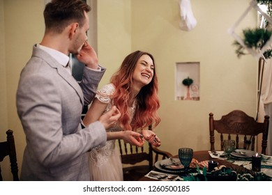 Wedding reception. Charming groom and bride with red hair cut wedding cake