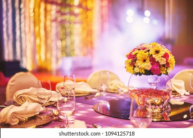 Wedding reception dinner table with flower bouquet decoration in the indian sangeet night with colorful lighting