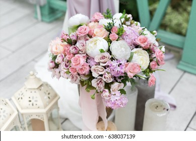 Wedding reception flower decorations, rustic style. Bridal bouquet and candles on wooden vintage background, outdoors, objects