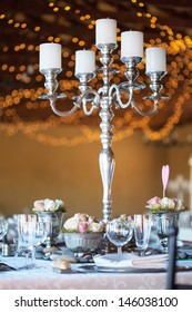 Wedding reception hall with decorated tables, selective focus with blurred fairy lights in background