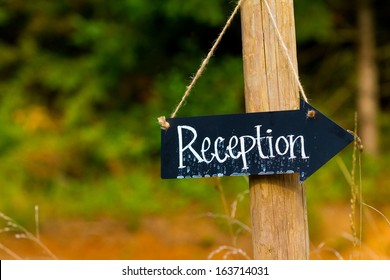 A wedding reception sign is made from a small chalkboard and has been outside in the rain. The sign is an arrow hung with twine.