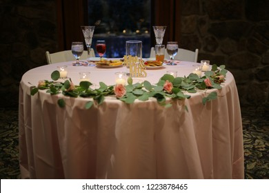 Wedding Reception Sweetheart Table with a Pink Table Cloth Decorated with a Garland of Eucalyptus Leaves and Pink Roses