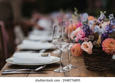 Wedding reception table banquet style with decoration, colorful flower bouquets, wine glasses on the wooden table in outdoor