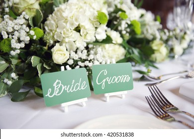 wedding reception table with center piece flower arrangement and bride and groom place cards