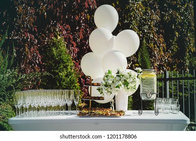 Wedding reception table with champagne, water and snacks, white balloons, vibrant background