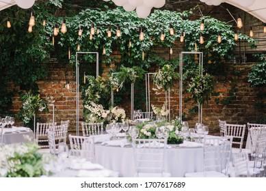 Wedding reception table with Edison bulbs and decor of greenery. Decoe. Wedding