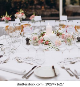 Wedding reception table in the restaurant decorated with white candles and flowers.