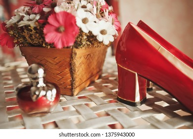Wedding red designer bride shoes, perfume bottle and decorative flowers in a basket on the coffee table. Women's new luxury modern fashion shoes made of shiny patent leather. Blurred background