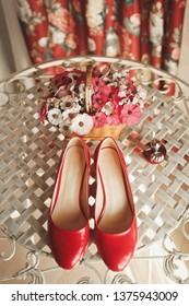 Wedding red designer bride shoes, perfume bottle and decorative flowers in a basket on the coffee table. Women's new luxury modern fashion shoes made of shiny patent leather. Wedding theme