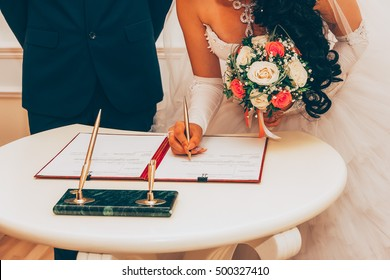 Wedding. Registration Of Marriage, The Bride With A Bouquet Of Flowers Signed A Marriage Contract A Golden Pen, Selective Focus. Tinted Image