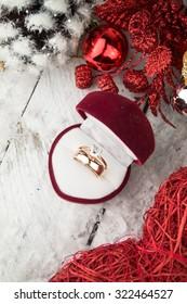 Wedding ring among Christmas decorations on wood background.