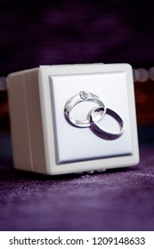 A wedding ring box with a emossed design of the bride and grooms ring interlinked.