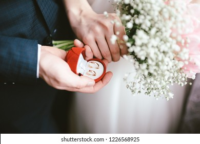 Wedding ring in a case and a bouquet of flowers