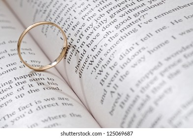 Wedding ring casts heart-shaped shadow on the book page