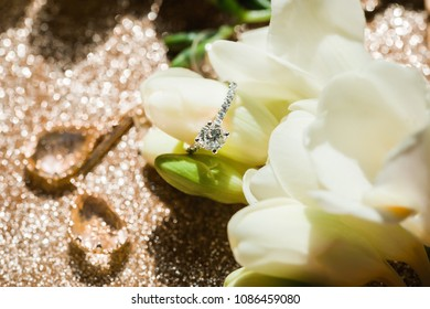 wedding ring on a flower with earnings on a gold background
