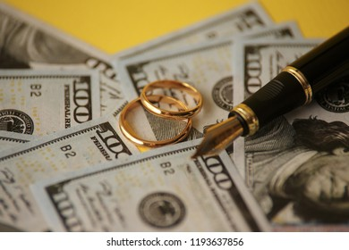 Wedding ring on pen, on banknotes background. Marriage of