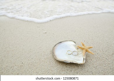 wedding ring on the shell by the beach