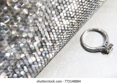 Wedding ring with silver handbag on white table.