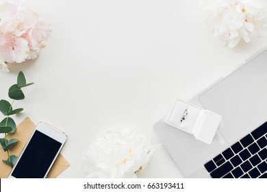 Wedding ring in a white gift box on the background of flowers and phone. top view