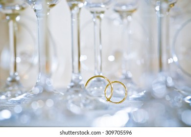 Wedding rings between wineglasses