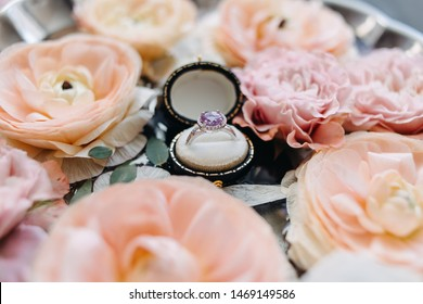 wedding rings in a black box and in a orange and pink flowers