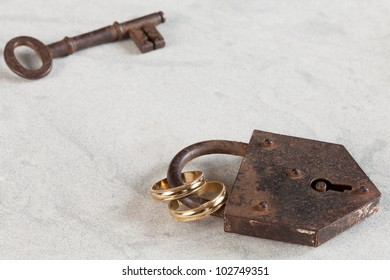 Wedding rings bound by a rusty lock