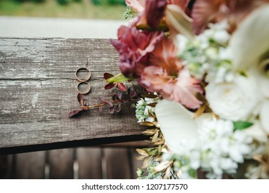 Wedding rings and a bouquet lie on a wooden surface