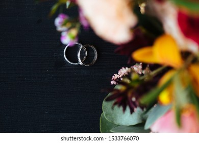 wedding rings and a bouquet on a dark background