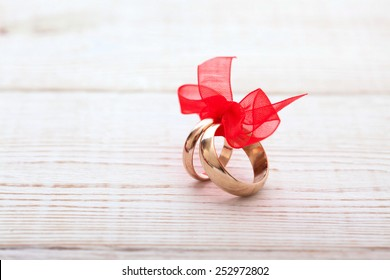 Wedding rings and wedding bouquet of red roses on wooden table. Selective focus, background is blurred, horizontally