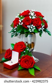 Wedding rings and wedding bouquet of red roses on wooden table