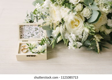 wedding rings in the box and a bouquet of the bride on the table