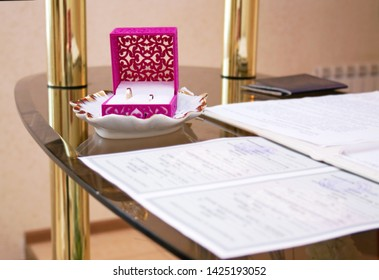 wedding rings in the box at the ceremony of marriage registration, marriage registration documents in the foreground, wedding attributes
