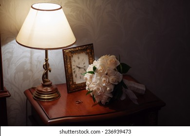 wedding rings in box on a nightstand with lamp