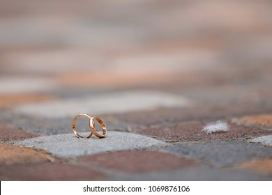 wedding rings of the bride and groom isolated on a wooden background.