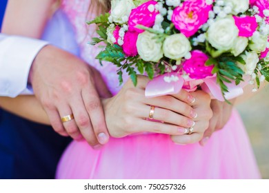 Wedding rings.  The bride is holding a bouquet