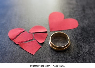 Wedding rings and broken red  heart. Black background. The concept of divorce, parting, infidelity .Selective focus.