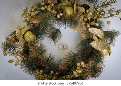 Wedding rings in the Christmas wreath on a wooden background, top view