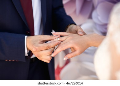 Wedding rings. Wedding day. Hands of bride and groom in solemn process of exchanging rings, symbolizing the creation of new happy family. Groom putting a ring on bride's finger during wedding ceremony