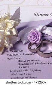 wedding rings with decorative flowers sitting on a ceremony program