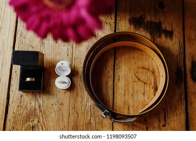 wedding rings a flower and a belt on a wooden table, set for a bridal couple