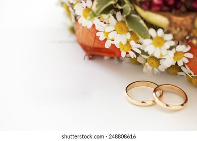 wedding rings and flowers on white background